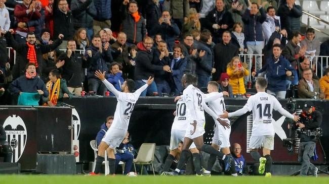 Bek Ezequiel Garay (kiri) merayakan gol Valencia ke gawang Real Madrid usai menerim umpan Daniel Parejo. (REUTERS/Heino Kalis)