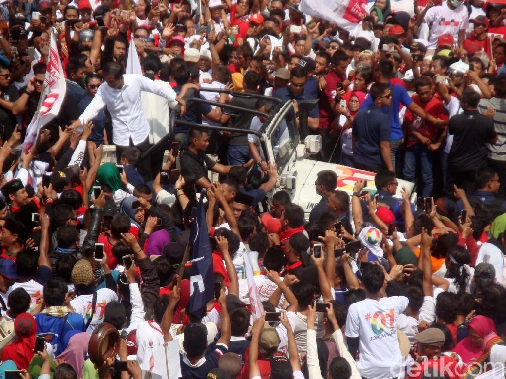 Jokowi bersama Iriana disambut meriah oleh para pendukung saat akan melaksanakan kampanye. Jokowi pun langsung menyalami para pendukung yang berdiri di sisi mobil Jeep yang ditumpanginya bersama Iriana.