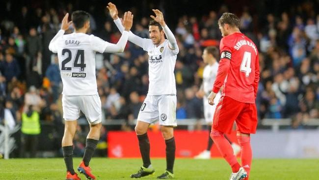 Kapten Valencia Dani Parejo (kiri) dan Ezequiel Garay merayakan kemenangan atas Real Madrid dengan Sergio Ramos tertunduk lesu. (REUTERS/Heino Kalis)