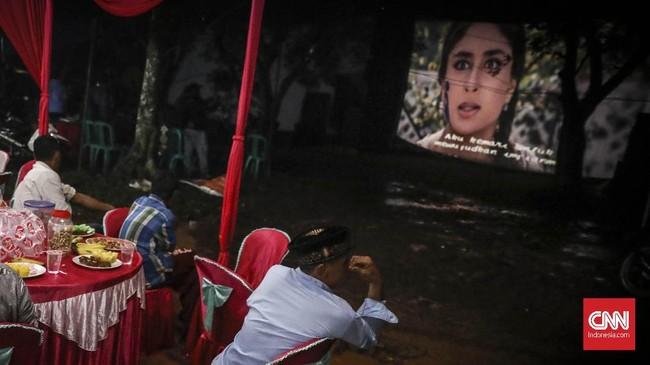 Suasana kumpul bareng saat menonton layar tancap menjadi hal yang tak bisa tergantikan oleh bioskop gedung. (CNN Indonesia/ Hesti Rika)