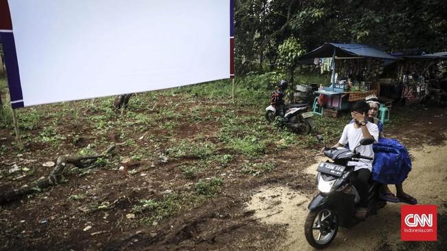Kain putih yang dijadikan layar dibentangkan di halaman pemilik hajat. Semalam suntuk film diputar hingga dini hari. (CNN Indonesia/ Hesti Rika)