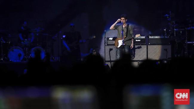 John Mayer adalah bintang utama di panggung malam hari itu, namun alih-alih tampil bagai musisi kenamaan pada umumnya dengan kostum mewah, ia tampil layaknya 'manusia biasa'. Malam itu, ia hanya mengenakan kaus polos berwarna hijau dan celana jeans. (CNNIndonesia/Safir Makki)