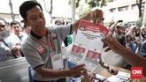 Pada tahap pengambilan surat suara, petugas memperlihatkan contoh surat suara kepada pemilih yang akan melakukan pencoblosan saat simulasi. (CNNIndonesia/Safir Makki)
