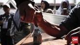 Usai mencoblos warga mencelupkan jari ke dalam botol tinta sebagai tanda telah melakukan pencoblosan dan menggunakan hak pilihnya dalam Pemilu 2019. (CNNIndonesia/Safir Makki)