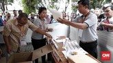 Petugas memeriksa kelengkapan semua alat dan berkas sebelum warga melakukan pencoblosan saat simulasi pemilihan suara Pemilu 2019. (CNNIndonesia/Safir Makki)