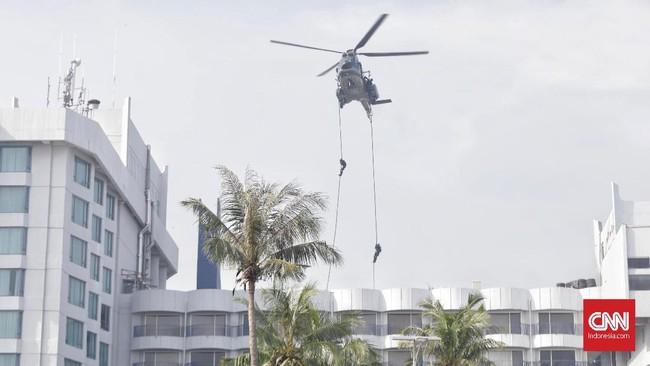 Simulasi operasi antiteror dibuka dengan aksi penembak jitu TNI yang melumpuhkan teroris yang berada di atap gedung dan garis pantai. Teroris tersebut menjadi sasaran pertama karena fungsinya sebagai mata kawanan teroris untuk memantau situasi di luar lokasi yang mereka kuasai. (CNN Indonesia/Adhi Wicaksono)