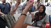 Warga yang akan mencoblos terlebih dahulu mendaftar di TPS dan menujukkan bukti kepada petugas bahwa jarinya belum tercelup tinta. (CNNIndonesia/Safir Makki)