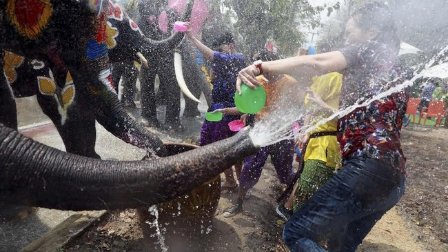 Secara tradisional ditandai dengan memberi hormat kepada para tetua dan menaburkan air di atas patung-patung Buddha di kuil-kuil setempat, saat ini Songkran berkembang menjadi pertarungan air yang heboh. (REUTERS/Soe Zeya)