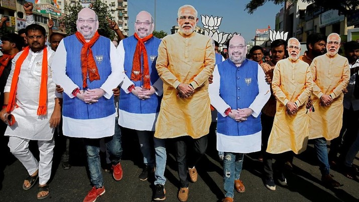 Supporter of India's ruling Bharatiya Janata Party (BJP) wearing cut-outs of Prime Minister Narendra Modi and the party president Amit Shah walk during an election campaign in Ahmedabad, India, April 11, 2019. REUTERS/Amit Dave     TPX IMAGES OF THE DAY