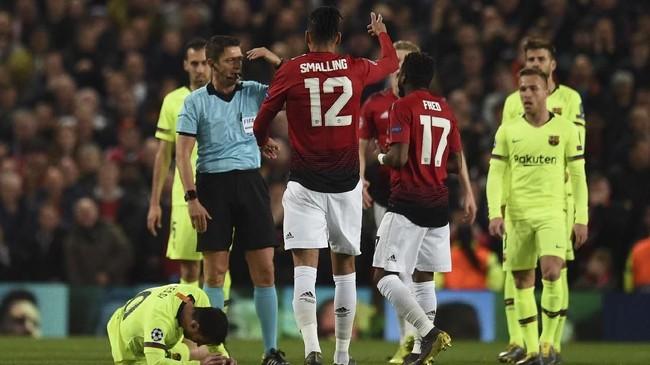 Laga memasuki menit ke-28, Chris Smalling menabrak Lionel Messi dalam perebutan bola udara. Tangan kanan Smalling kemudian mengenai wajah La Pulga. (Oli SCARFF / AFP)