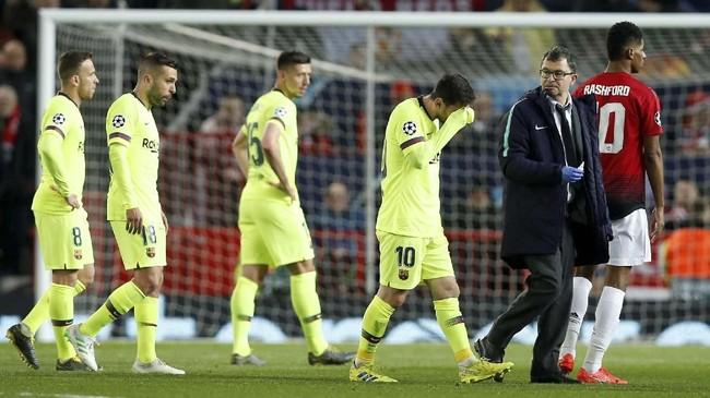 Lionel Messi kemudian berjalan ke pinggir lapangan untuk mendapat perawatan medis usai ditabrak Chris Smalling. (REUTERS/Andrew Yates)
