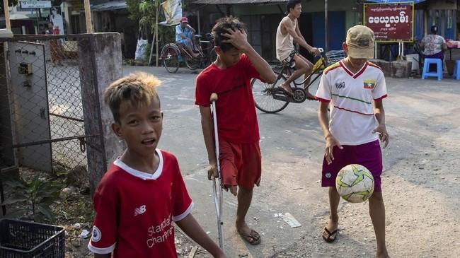 Meski salah satu kakinya tidak normal dan harus menggunakan kruk untuk berjalan, Kaung Khant Lin kerap bermain sepak bola bersama rekan-rekannya di daerah pinggiran Yangon. (SAI AUNG MAIN / AFP)