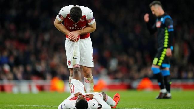 Sokratis Papastathopoulos membantu Ainsley Maitland-Niles untuk meredakan masalah di kaki. Arsenal menang 2-0 pada leg pertama dan akan bertamu ke markas Napoli pekan depan. (REUTERS/Eddie Keogh)