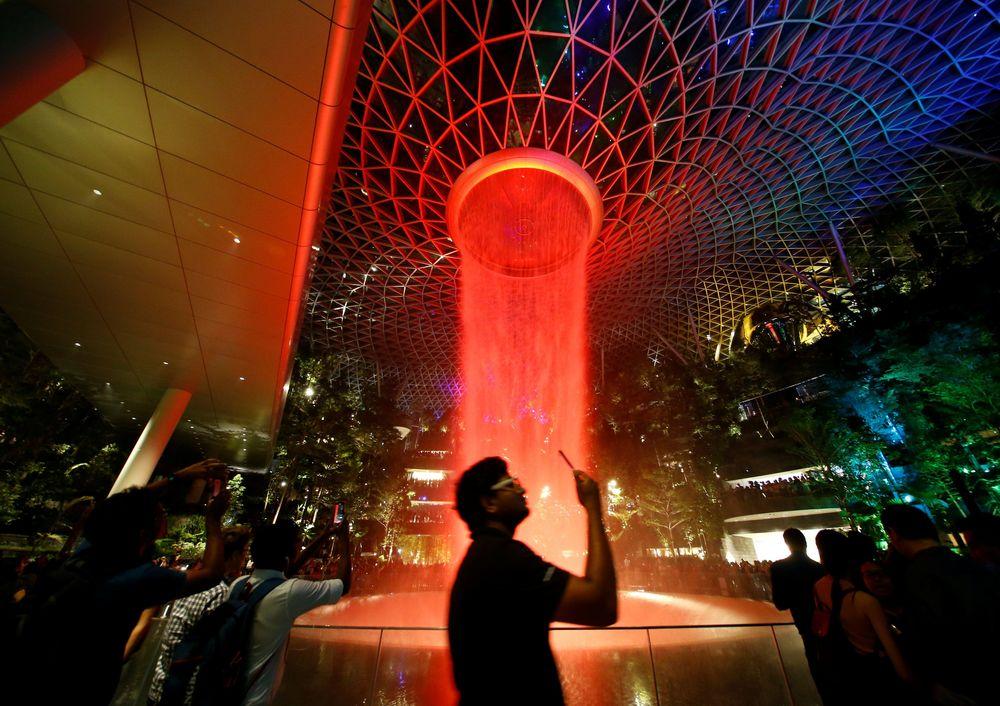 Pada malam hari, Rain Vortex akan dipenuhi oleh cahaya yang menyala. Selain sebagai portal ke bandara, bangunan seluas 134.000 meter persegi yang terbuat dari kaca ini dimaksudkan untuk menjadi tujuan ritel dan hiburan.(REUTERS / Feline Lim)
