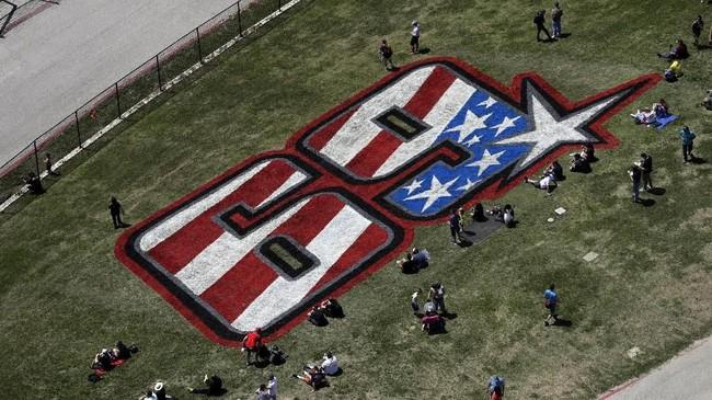 Penonton duduk di sekitar tribute untuk mendiang legenda balap MotoGP asal Amerika Serikat Nicky Hayden di Sirkuit Americas pada hari pertama MotoGP Amerika 2019, Jumat (12/4) siang waktu setempat. (AP Photo/Eric Gay)
