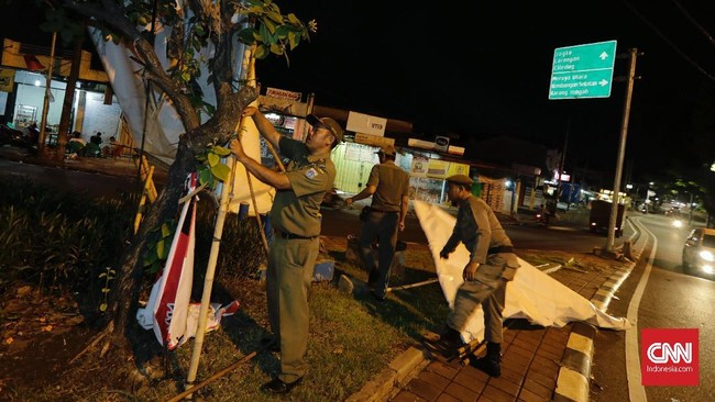Penertiban Alat Peraga Kampanye (APK) dilakukan karena Pemilu kini telah memasuki masa tenang yaitu pada 14 hingga 16 April. (CNNIndonesia/Adhi Wicaksono)
