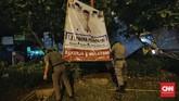 Petugas Satpol PP bersama Aparat Kepolisian dan PPSU menertibkan baliho dan spanduk caleg yang terpasang di wilayah Jakarta Barat, Minggu (14/4) dini hari. (CNNIndonesia/Adhi Wicaksono)