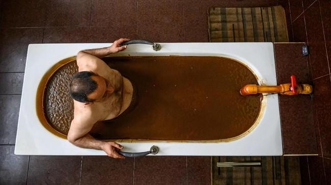 Salah satunya adalah di Pusat Kesehatan Sehirli. Di sana tersedia bak mandi besar berisi minyak mentah yang siap menemani mandi Anda. (Photo by Mladen ANTONOV/AFP)