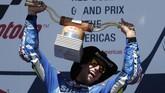 Alex Rins mengangkat trofi podium pertama MotoGP Amerika Serikat. Sukses itu menandai kemenangan perdana mereka di MotoGP sepanjang kariernya. (AP Photo/Eric Gay)