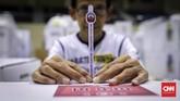 Petugas Kelompok Panitia Pemungutan Suara (KPPS) di Gudang Logistik KPU Kecamatan Tanah Abang, Jakarta, memastikan tidak ada kerusakan di setiap item logistik, mulai dari surat suara, kotak suara, bilik suara, sampul surat suara hingga kelengkapan alat seperti spidol, pulpen, dan tinta. (CNNIndonesia/Safir Makki).