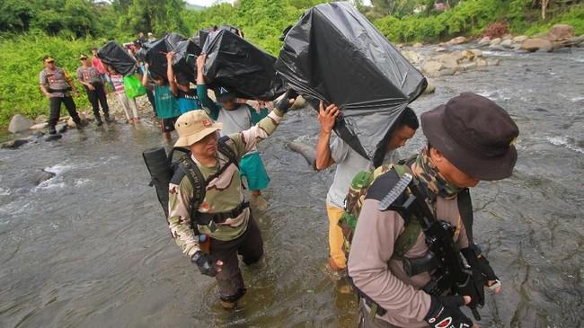 Personel Polri mengawal sejumlah pekerja pengangkut barang (porter) menyeberangi sungai saat membawa logistik Pemilu serentak 2019 ke dua desa terpencil di kaki Pegunungan Meratus, Kabupaten Hulu Sungai Tengah, Kalimantan Selatan, Minggu (14/4). (ANTARA FOTO/Bayu Pratama S/wsj).