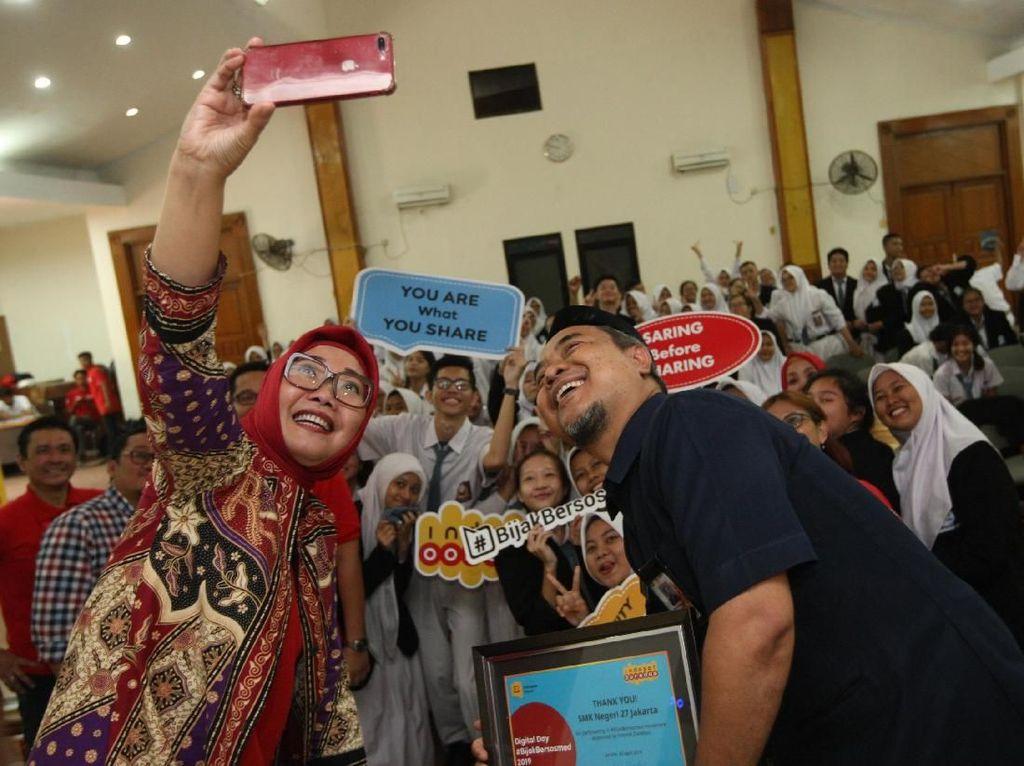 Group Head Corporate Communications Indosat Ooredoo, Turina Farouk (kiri), Wakil Kepala Sekolah Bidang Kurikulum SMK Negeri 27 Jakarta, Agus Susanto (kiri) berfoto bersama siswa-siswi SMK Negeri 27 Jakarta seusai peluncuran program CSR Digital Day #BijakBersosmed di Jakarta (15/4). Istimewa.