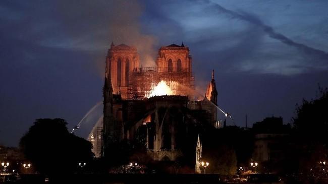 Anggota pemadam kebakaran Prancis menyelamatkan sejumlah artefak di Gereja Notre-Dame setelah si jago merah nyaris menghancurkan seluruh bangunan. (REUTERS/Benoit Tessier)