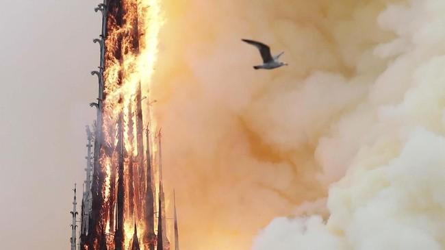 Tugu di atas atap Gereja Notre-Dame akhirnya roboh karena dilalap api. (REUTERS/Benoit Tessier)