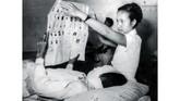 Seorang juru rawat sebagai wakil PPPS tengah melayani pemilih dengan membentangkan surat suara di Rumah Sakit Umum Rancabadak, Bandung 15 Desember 1955. (Sumber: ANRI)