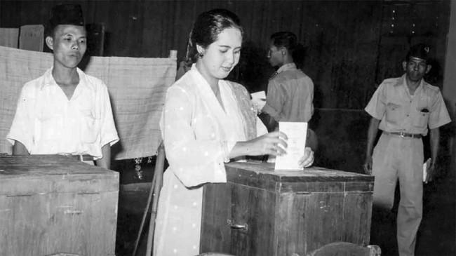Pemilu 1955 dilakukan dua kali, 29 September untuk memilih anggota DPR, dan 15 Desember untuk memilih anggota konstituante. Ibu Rahmi Hatta sedang memasukan surat suaranya ke dalam kotak suara di TPS gedung olah raga, Jakarta 15 Desember 1955. (ANRI)