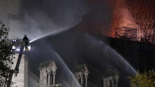 Asap terlihat mengepul keluar dari bagian atas katedral yang dibangun pada abad pertengahan tersebut. Api menjalar di samping dua menara lonceng. (REUTERS/Charles Platiau)