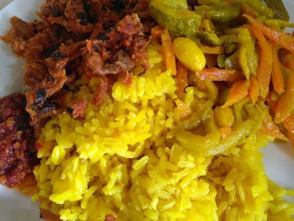 Meski lauknya hanya cakalang rica dan acar kuning, dijamin puas menyantap nasi kuning yang satu ini. Foto: Instagram @popyervina