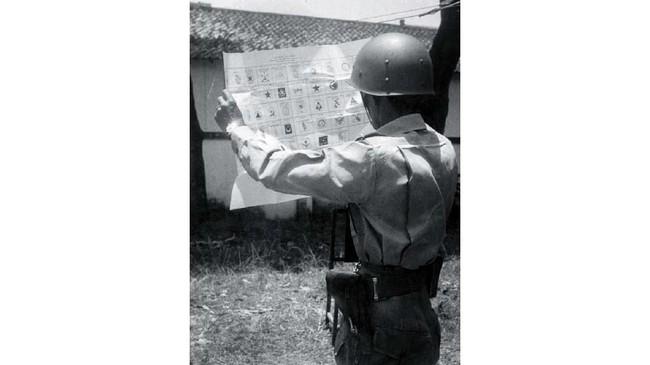 Seorang anggota APRI sedang memperhatikan surat suara yang bergambar lambang-lambang partai politik sebelum dicoblos, 29 September 1955. (Sumber: ANRI)