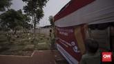 Petugas dan warga mendirikan tempat pemungutan suara (TPS) 034 RW 07 di kawasan TPU Karet Bivak. Jakarta, Selasa (16/4). (CNN Indonesia/Adhi Wicaksono)