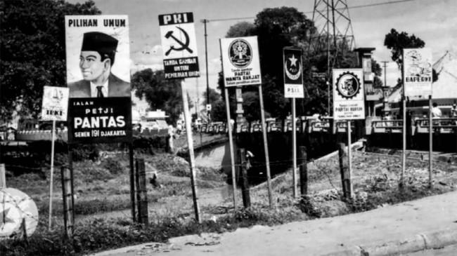 Pemilu 1955 diadakan di tengah suasana keamanan negara yang tidak kondusif akibat banyaknya pemberontakan. Tampak papan gambar partai-partai dalam pemilu yang dipasang di tepi jalan, di Jalan Prapatan Kwitang Jakarta, 24 Juli 1955. (Sumber: ANRI)