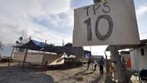Petugas dan warga bergotong-royong mendirikan tempat pemungutan suara (TPS) di lokasi terdampak bencana gempa dan tsunami di Mamboro, Palu, Sulawesi Tengah, Selasa (16/4). Meski baru dilanda bencana gempa dan tsunami pada 28 September 2018, warga di daerah tersebut tetap menyambut pesta demokrasi. ANTARA FOTO/Mohamad Hamzah