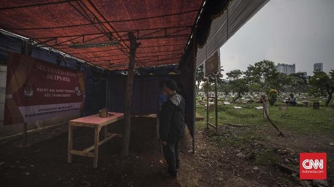 Petugas dan warga mendirikan tempat pemungutan suara (TPS) 034 RW 07 di kawasan TPU Karet Bivak. Jakarta, Selasa, (16/4). (CNN Indonesia/Adhi Wicaksono)