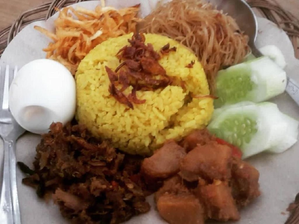 Gaya sajian nasi kuning rumah kopi Gembira Kawangkoan di Jakarta. Lauknya komplet. Mari makan! Foto: Instagram @kopigembira1946