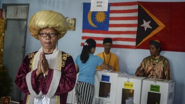 Petugas KPPS membantu warga untuk memberikan hak suaranya di TPS 24 yang bertemakan Konferensi Asia Afrika di Kecamatan Astana Anyar, Bandung, Jawa Barat. Tema Konferensi Asia Afrika tersebut diambil dalam rangka memperingati Hari Asia Afrika pada 18 April mendatang. (ANTARA FOTO/Raisan Al Farisi)
