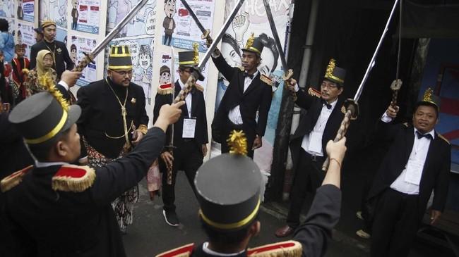 Petugas KPPS menyambut warga yang akan menggunakan hak pilihnya dengan prosesi pedang pora di TPS 27 Kampung Happy, Manahan, Solo, Jawa Tengah, Rabu (17/4). Aksi tersebut merupakan bentuk antusiasme warga setempat menyambut pesta demokrasi Pemilu 2019. (ANTARA FOTO/Maulana Surya)