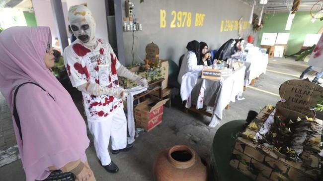 Di TPS yang bertemakan 'horor' di Jakarta, para petugas menggunakan perban dan juga pakaian yang menyerupai hantu. (Photo by Demy Sanjaya / AFP)