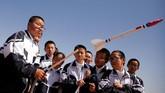 Seorang siswa melakukan uji coba dengan meluncurkan roket mainan di Gurun Gobi. (REUTERS/Thomas Peter)