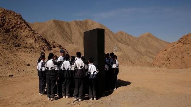 Para siswa berkumpul di sekitar lempengan hitam yang mewakili materi dari Mars di Gurun Gobi, pangkalan simulasi C-Space Project Mars, China. (REUTERS/Thomas Peter)