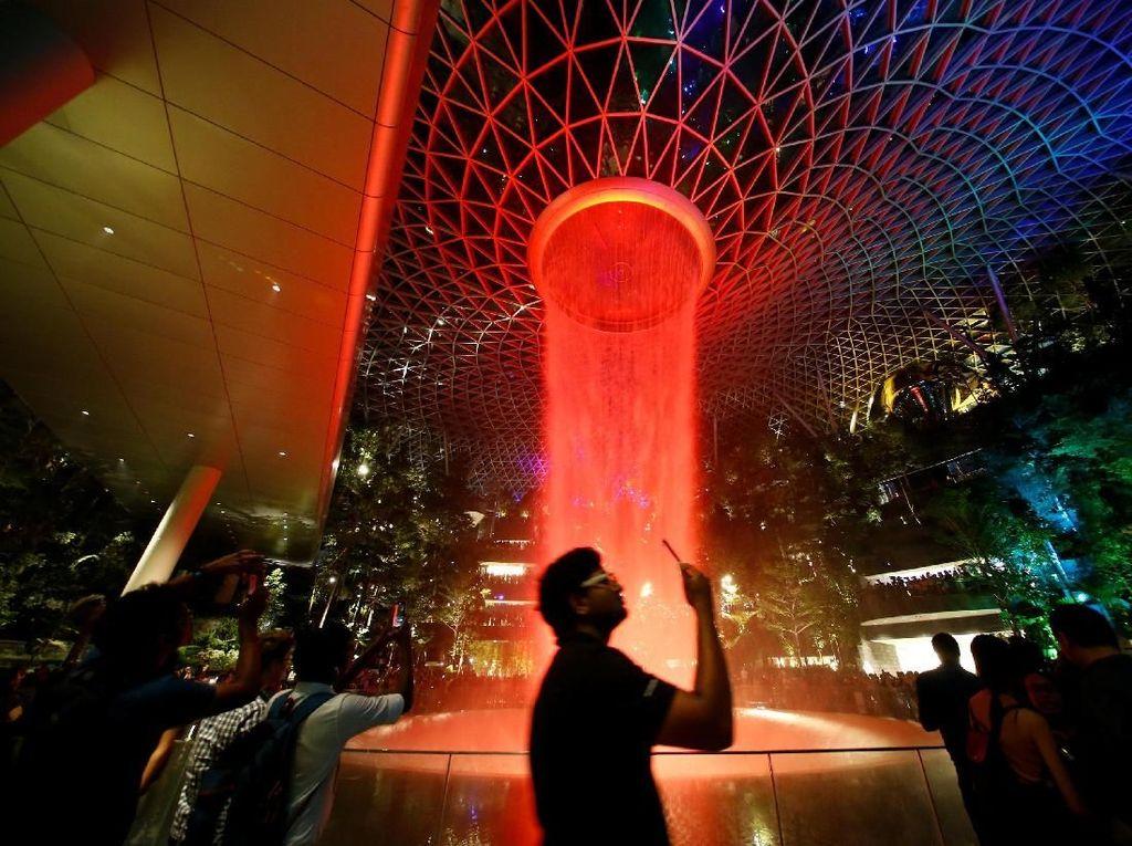 Orang-orang menonton layar cahaya di Rain Vortex setinggi 40 meter, yang merupakan air terjun indoor tertinggi di dunia, terlihat dari dalam Bandara Jewel Changi di Singapura.