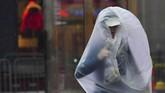 Seorang pelari coba menjaga agar tubuhnya tetap kering ketika mengikuti Marathon Boston di Massachusetts, Amerika Serikat. (REUTERS/Gretchen Ertl)