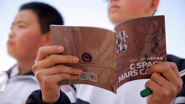 Siswa mendengarkan pelajaran mengenai hidup di kapsul ruang angkasa tiruan yang berada di Gurun Gobi. (REUTERS/Thomas Peter)