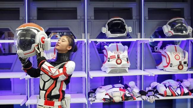 Seorang anggota staf mendemonstrasikan bagaimana dia mengenakan helm dan setelan baju tiruan untuk hidup di Mars. (REUTERS/Thomas Peter)