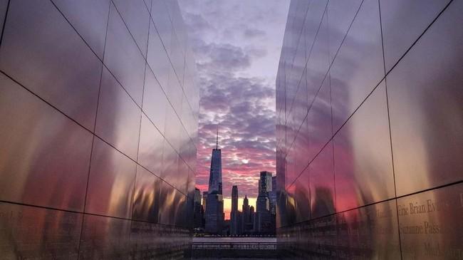 Sinar mentari pagi menerangi langit kota New York dan terlihat dibingkai oleh memorial Empty Sky di area Jersey City. (AP Photo/J. David Ake)