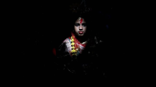 Seorang gadis yang berpakaian seperti seorang Dewi duduk dalam suatu ritual yang merayakan festival Navratri di kuil Adyapeath di luar kota Kolkata, India. (REUTERS/Rupak De Chowdhuri)