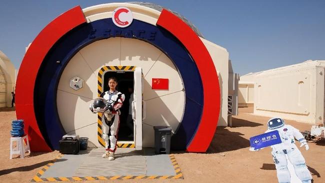 Seorang anggota staf berpose dalam setelan ruang angkasa tiruan di pangkalan simulasi C-Space Project Mars. (REUTERS/Thomas Peter)